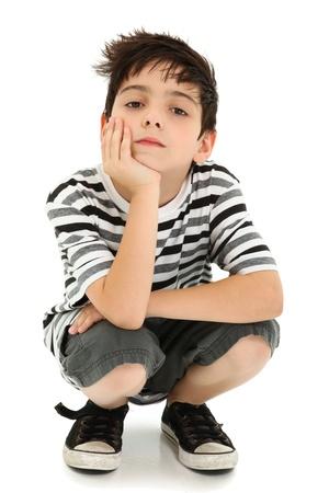 squatting: Ni�o con ment�n descansando por parte con vigilancia de expresi�n blanco. Foto de archivo