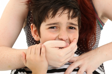 overpowered: Scared 8 year old boy being abused or abducted by adult female. Stock Photo