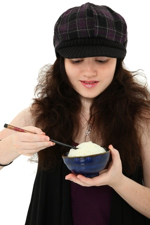 18 year old: Attractive 18 year old young woman in hat eating bowl of rice with chopsticks over white.