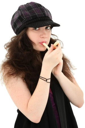 18 year old: Attractive 18 year old girl in hat over white eating mozzarella  string cheese.