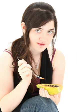 over eating: Attractive young woman eating a papaya fruit over white background.