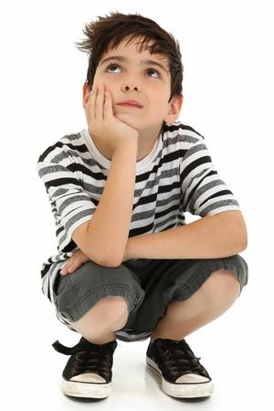 squatting: Ni�o 8 a�os atractivo lo expresi�n de pensamiento sobre blanco.