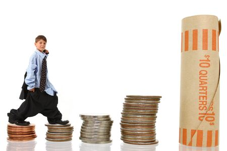 Attractive young boy in suit climbing up stack of giant usd coins over white.