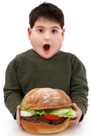 Hungry obese child with giant hamberger over white. photo