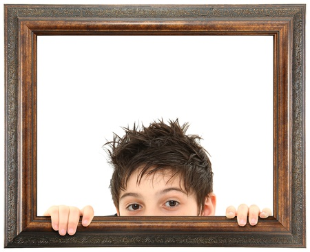 Attractive 8 year old boy peeking out of ornate stained wooden frame over white isolation.