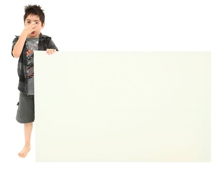 Attractive 8 year old boy holding blank white sign making stinky face expression. photo