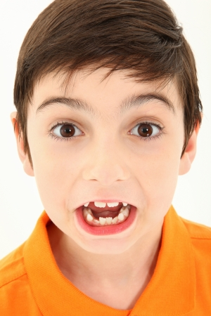 crooked teeth: Attractive 8 year old boy close up making silly face.
