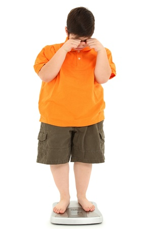 Morbidly obese fat child on scale crying.