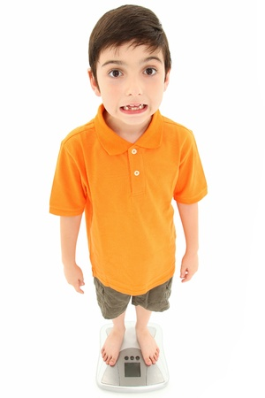 Attractive 8 year old boy making silly faces and weighing self on scale.