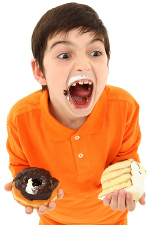 Attractive 8 year old boy with insane expression and hands full of sweets over white. Standard-Bild