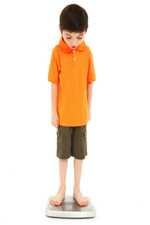 underweight: Adorable eight year old boy on scale very thin anorexia nervosa childhood onset concept.
