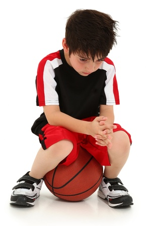 sad child: Sad elementary school boy sitting on basketball sad crying expression on face. Stock Photo