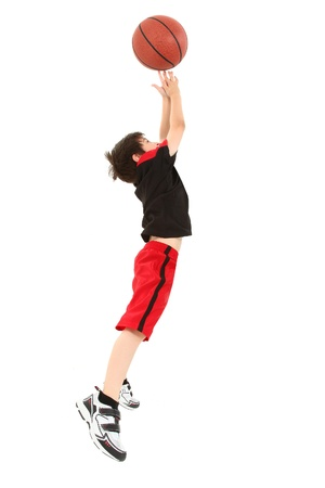 Energetic 8 year old boy child in basketball uniform jumping for shot.