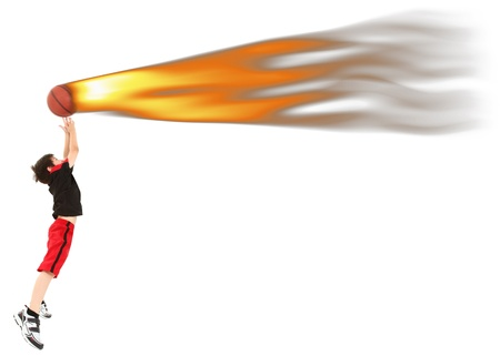 Energetic 8 year old boy child in basketball uniform jumping to catch bal on fire. photo