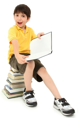 literate: Adorable elementary age school boy child making faces on stack of books.