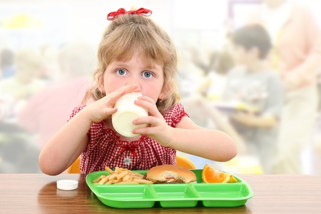 Elementary school girl child having cafeteria lunch at table. photo