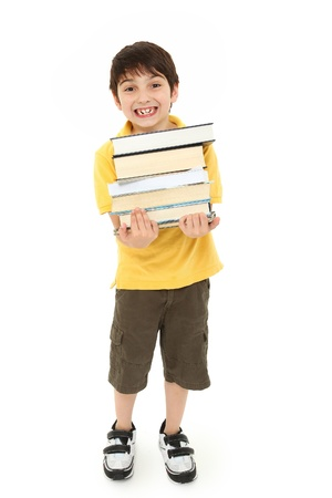 Adorable back to school boy child with stack of text books in arms walking over white background. Imagens