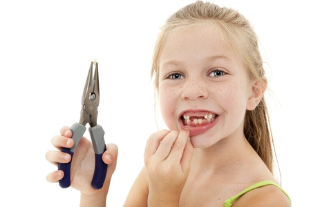 Close up adorable young girl with missing teeth pulling tooth out with pliers. Stock Photo