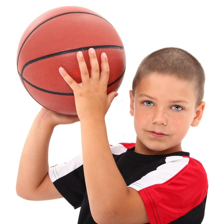 Adorable male child with basketball in uniform over white background. Stock Photo