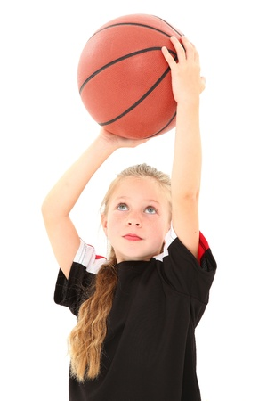 Adorable female child making free throw with basketball in uniform over white background.