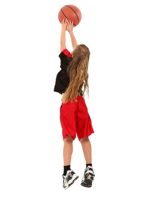 Girl child basketball player jumping for ball over white background in uniform.