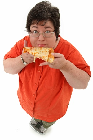 Happy confident obese forty-five year old woman on scale with slice of cheese pizza over white. photo
