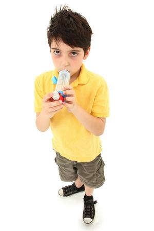asma: Ni�o enfermo joven usando el inhalador para el asma con c�mara espaciadora en blanco.  Tiene hiperpigmentaci�n periorbitales.