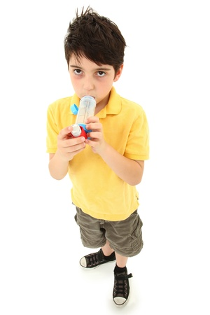 asthma: Sick young boy child using asthma inhaler with spacer chamber over white.  Has periorbital hyperpigmentation. Stock Photo