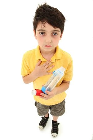 asthma: Young asthmatic child with inhaler and spacer chamber over white background. Stock Photo