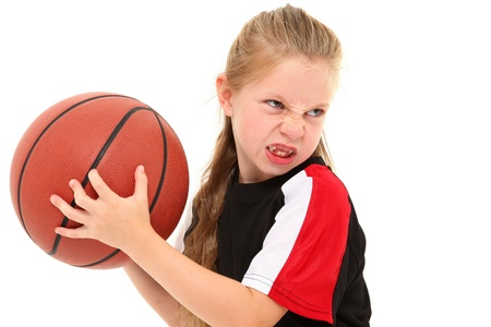 Serious girl child basketball player in uniform throwing ball between legs over white background.