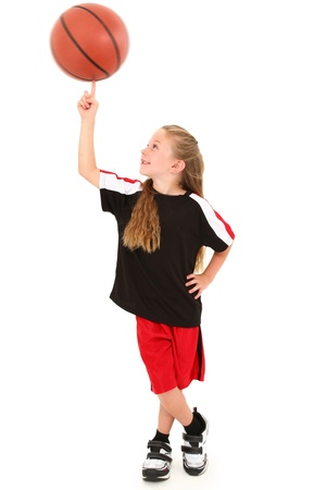 Proud young girl child basketball player in uniform spinning ball on finger over white background.
