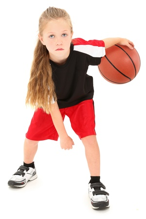 Serious girl child basketball player in uniform dribbling ball between legs over white background. photo