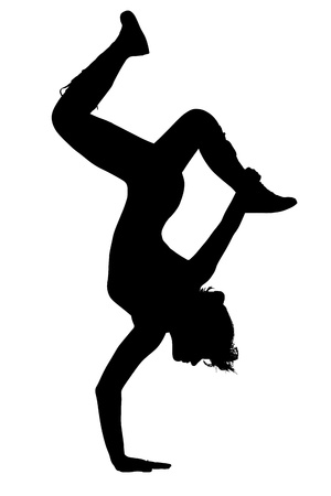 Silhouette of teen girl dancing upside down on one hand