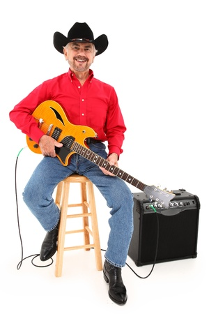 amps: Attractive elderly country musician with electric guitar, boots, cowboy hat at age 75 over white background.
