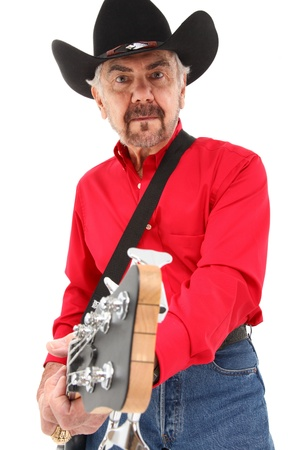 Handsome eldery 75 year old country musician with electric bass guitar and cowboy hat over white background. photo