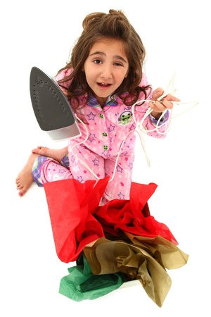 stupid body: Adorable young girl child opening a really bad gift over white background.  Disapointed expression.