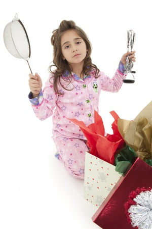 Girl child opening bad christmas gift over white with disapointed sad expression. 免版税图像