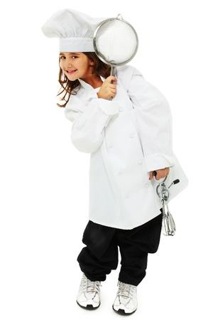 batidora: Adorable ni�a de nueve a�os de edad, de pie en uniforme del cocinero holgada sobre blanco con batidor de huevos y el skimmer.