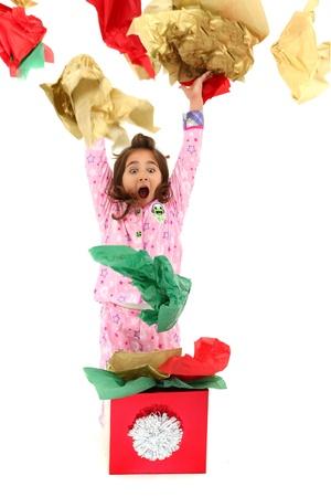 squeal: Eccitato bambina giovane, gettando carta da imballaggio in aria. Apertura di Natale o regalo di compleanno. Archivio Fotografico