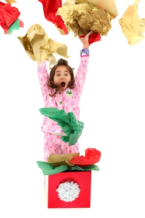 Excited young girl child, throwing wrapping paper into the air.  Opening Christmas or Birthday gift.