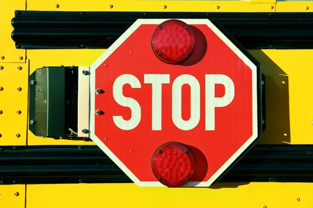 Close up of red stop sign on yellow school bus. photo