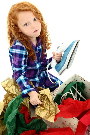Angry dissapointed girl child receiving an iron as a gift.  Over white background. photo