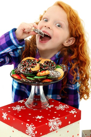 Beautiful Excited Girl Child in Pajamas with a Tray of Holiday Cookies over white background.  Archivio Fotografico