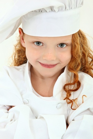 Beautiful young girl child wearing chef uniform and baker hat over white. Arms crossed, smiling.