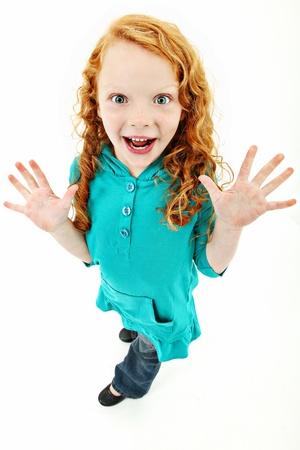 흥분된 식 흰색 배경 위에 서있는 사랑스러운 어린 소녀. 스톡 콘텐츠
