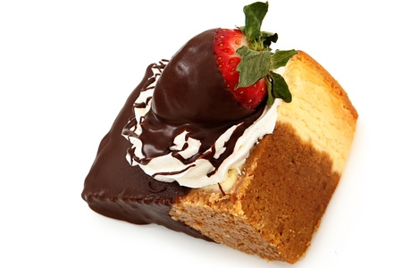 Single slice of cheesecake with strawberry and whipped topping dipped in chocolate ganache over white.