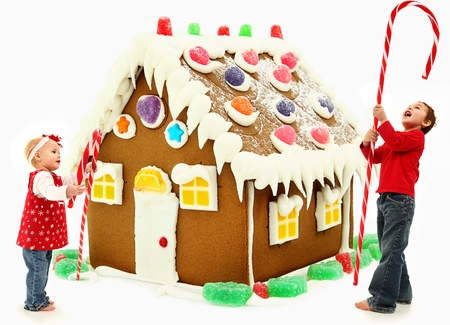 Young brother and sister building a giant gingerbread house together. Imagens