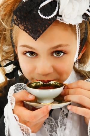 tea hot drink: Beautiful Tween Girl in Cosplay Fashion Sipping Tea Stock Photo