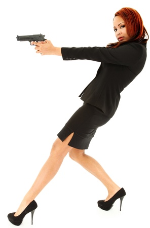 Beautiful Black Woman in Suit and Heels Aiming Handgun in studio over white