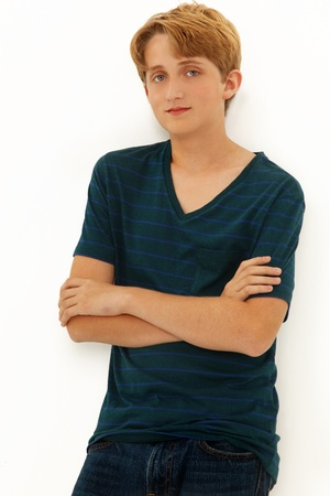 Attractive Teen Boy Caucasian leaning on wall with arms crossed.
